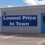 the endcap of a single story metal storage building with a sign spelling out Lowest Price in Town