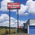 a tall sign that reads Carmichael Mini Storage and a single storage unit door on the right