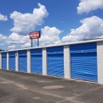 a row of self storage units with doors closed and a sign reading Carmichael Mini Storage in the background under a blue sky